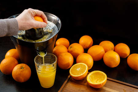 Juicing a fresh and healthy orange. Healthy lifestyle concept. Stock Photo