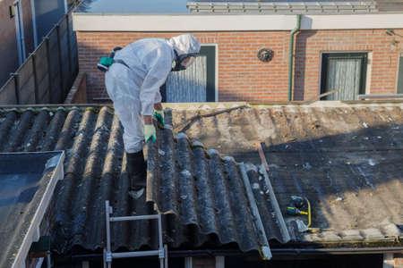 Professionele asbestverwijdering. Mannen in beschermende pakken verwijderen asbestcement golfplaten dakbedekking Stockfoto