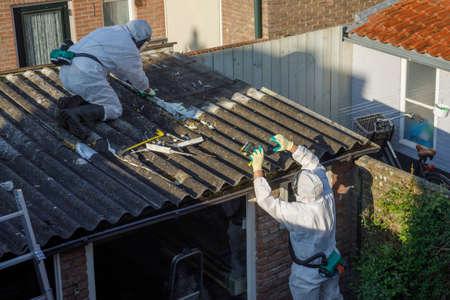 Rimozione amianto professionale. Uomini in tute protettive stanno rimuovendo il tetto ondulato in cemento amianto