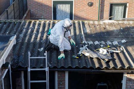 Eliminación de amianto profesional. Hombres con trajes de protección están quitando los techos corrugados de fibrocemento