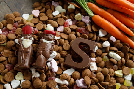 Dutch candy called Pepernoten eaten during Sinterklaas feast. Beside it carrots to be given to the horse of Sinterklaas
