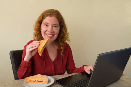 Causasian woman enjoying breakfast or lunch while working or learning at home Standard-Bild
