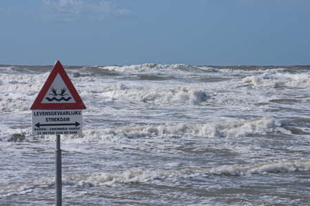 A sign warns for the risk of drowning by dangerous currents cause by a dam in the sea