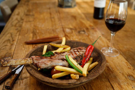 Tomahawk steak with fries, vegetables and a glass of red wine on a wooden table with medieval tableware.