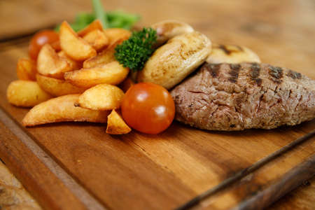 A delicious steak, fries and green beans on a wooden cutting board Standard-Bild