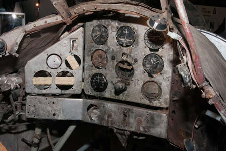 Remains of the cockpit of a crashed world war two fighter with broken gauges. Labels tell which gauges are missing