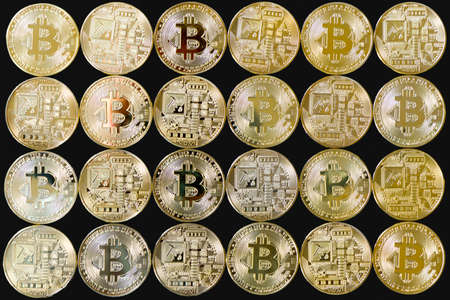 A photo of golden bitcoins with various reflections. Isolated on a black background Standard-Bild