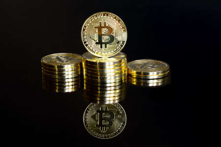 Golden bitcoins stacked as a winner podium. Isolated on a black background with reflection Standard-Bild