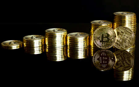 Golden bitcoins stacked as a graph. With reflection on a black background.