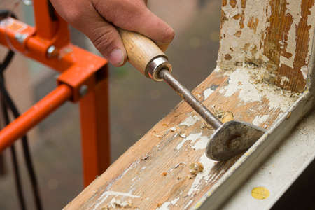 House renovation. A painter removing old paint with a scraper.