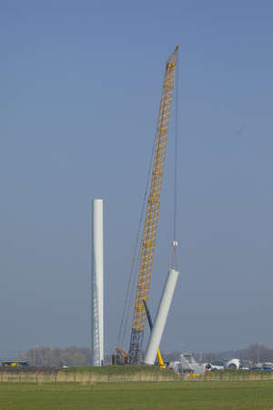 Construction workers preparing the rotor blades of a new wind turbine.