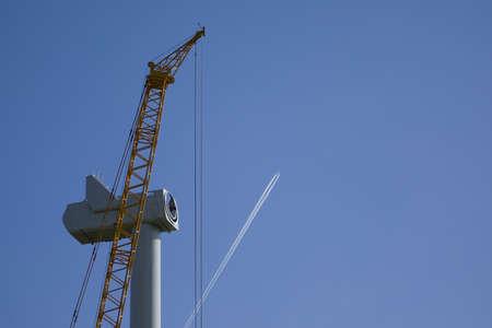 An passenger aircraft is drawing contrails behind a wind turbine under construction Standard-Bild