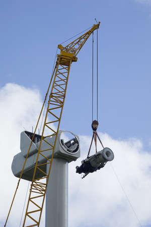 A crawler crane is hoisting the gearbox of a new wind turbine Standard-Bild
