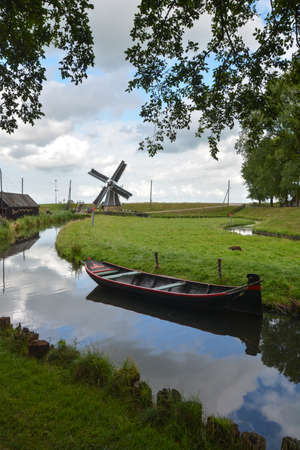 old windmill and boat on small canal photo
