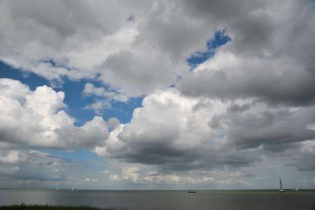cloudscape above lake with boats photo
