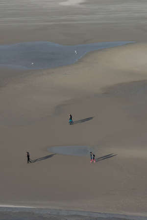 unrecognizable small people walking on the beach photo