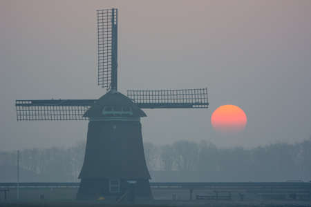 sunrise misty winter morning with windmill photo