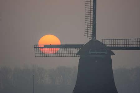sunrise misty winter morning with windmill photo