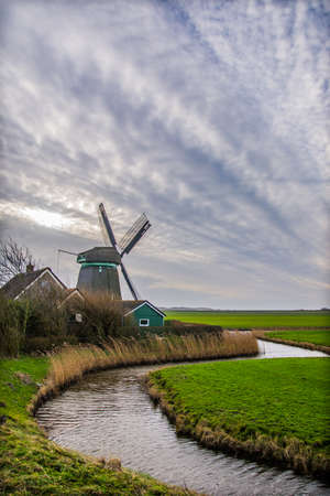 old dutch windmill with windy sky and canal photo