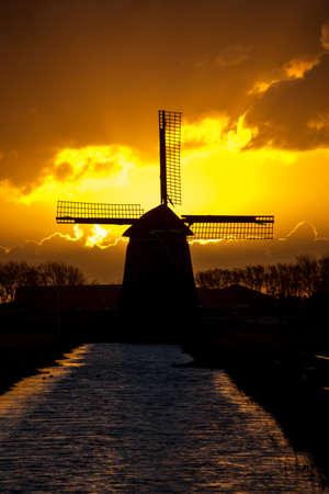 iluminado a contraluz: retroiluminada molino de viento holandés durante el amanecer