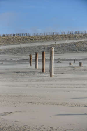 dyke: beach with wooden poles and sand dunes Stock Photo