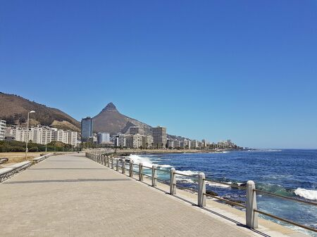 Mountains, hotels and deep blue water with waves at the Sea Point, beach promenade in Cape Town South Africa. Stock Photo