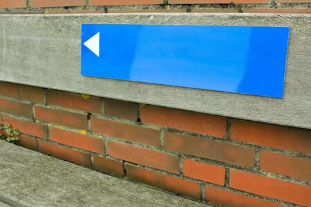 Blue sign with arrow on brick wall. Empty as a texture. Stock Photo