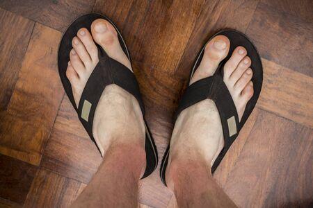 Brown flip flops on brown floor texture background. Vacation clothes. Stock fotó