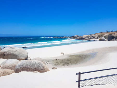 Camps Bay Beach behind fence and rocks in Cape Town. 免版税图像