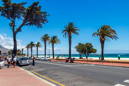 Street with palm trees and beach in Camps Bay, Cape Town. Stock Photo