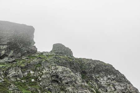Striking rock formation cliffs with fog and clouds on Veslehødn Veslehorn mountain in Hemsedal, Norway.