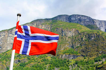 The national flag of Norway in the rough wind and blue sky with clouds.