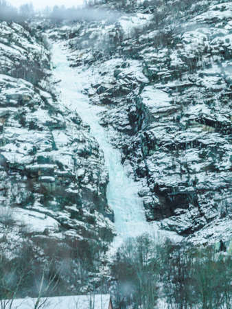 Frozen waterfall and icicles in a beautiful landscape in Norway.