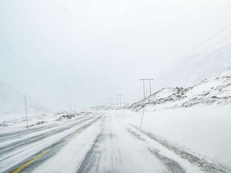 Driving through blizzard snowstorm on black ice and snowy white road and landscape in Norway. Stock Photo