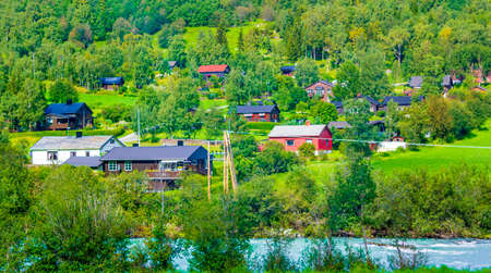 Turquoise meltwater flows in a river through a village in Norway. Stock fotó