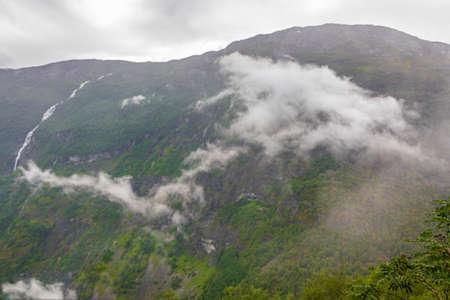 Fog mist clouds rain and waterfall on mountain in norwegian landscape Utladalen Norway.