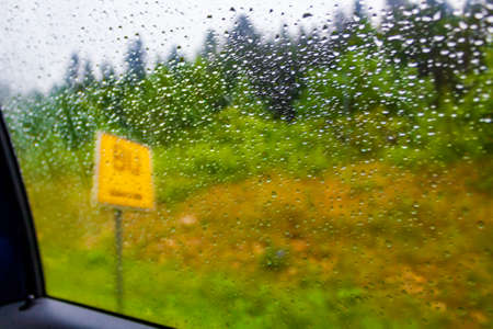 Yellow place-name sign behind a rainy car window in Austria.