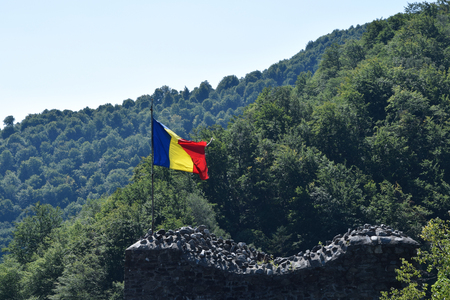Romanian flag waving in the wind at the ruin of Poenari Castle. Romania National Flag.