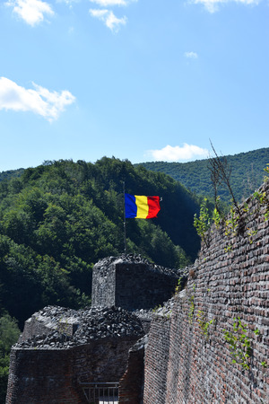 Romanian flag waving in the wind at the ruin of Poenari Castle. Romania National Flag.