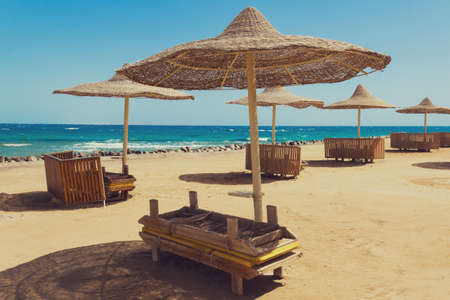 slack: Deserted beach with wattled sun umbrellas on a seashore. Stock Photo