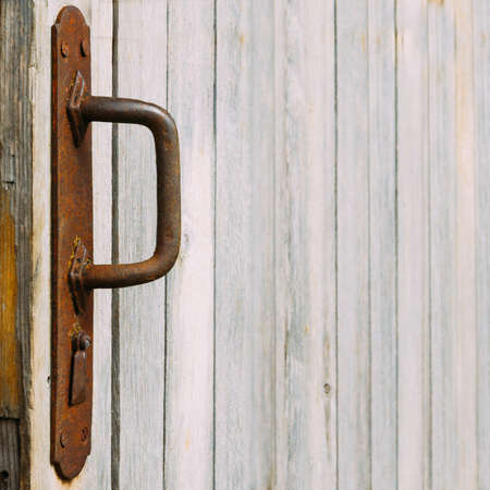 rusts: Rusted handle and old wooden wall. Texture. Background. Square.