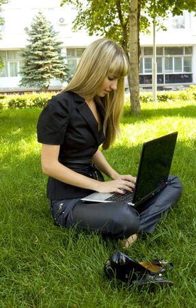 The girl in black, on the lawn with a laptop photo
