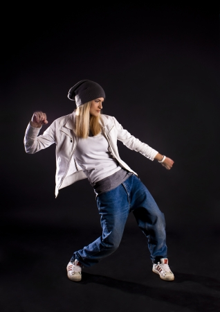 Modern dance, hip hop girl dancer on a black background.