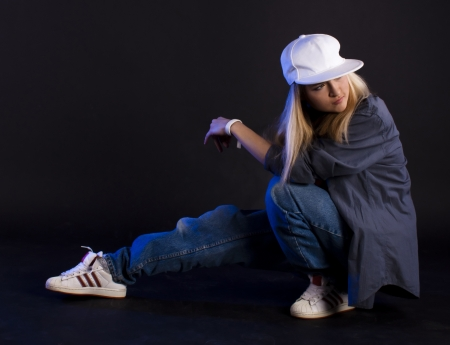 Modern dance, hip hop girl dancer on a black background. photo
