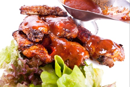 A dish of chicken wings with sauce and greens on a white background photo