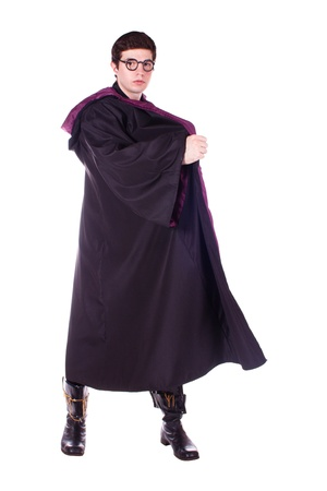 A man dressed as a magician in a black cloak. White background.