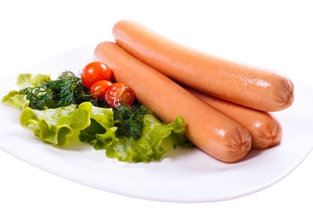 sausages on a plate with vegetables and greens, white background