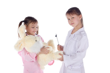 girl, a doctor, the child, rabbit toy. Children dressed as doctors, nurses photo
