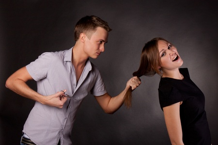 male hairdresser maniac, mocks a woman.  black Background Stock Photo