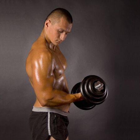 Muscled male bodybuilderweight, dumbbell, raise, swing Stock Photo - 13801877